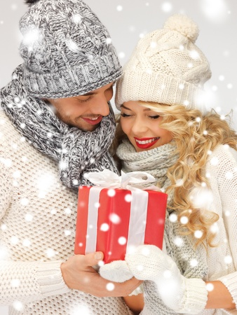 couple cuddling: picture of romantic couple in a sweaters with gift box