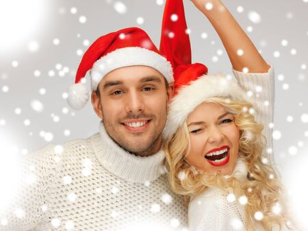 santas  helper: picture of family couple in sweaters and santa s hats Stock Photo