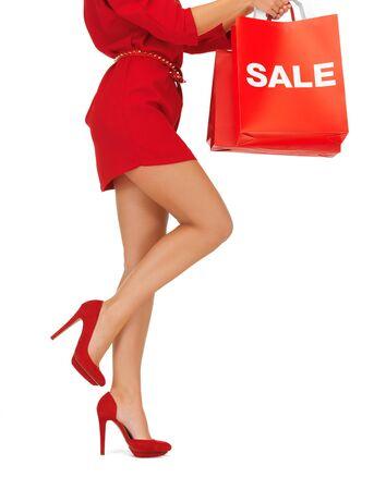 tacones rojos: Primer plano retrato de mujer en tacones altos con sus bolsas de compras Foto de archivo