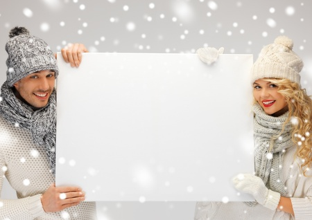 shawl: picture of family couple in a winter clothes holding blank board Stock Photo