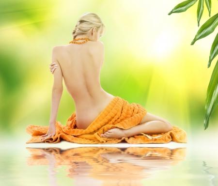 tratamientos corporales: mujer hermosa en balneario con las toallas sobre verde Foto de archivo