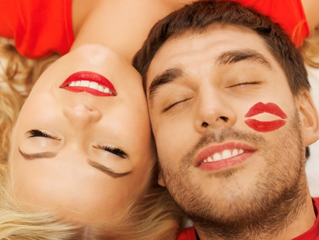 lipstick kiss: happy couple lying at home with closed eyes  focus on woman