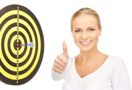 confident businesswoman with dart and target showing thumbs up   photo