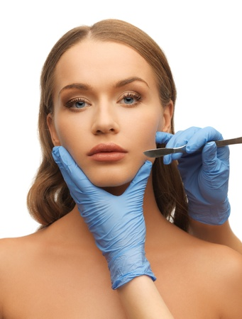 picture of woman face and beautician hands with scalpel photo