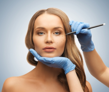 surgery doctor: picture of woman face and beautician hands with pencil Stock Photo