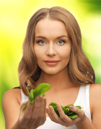 bright picture of woman with spinach leaves on palms photo
