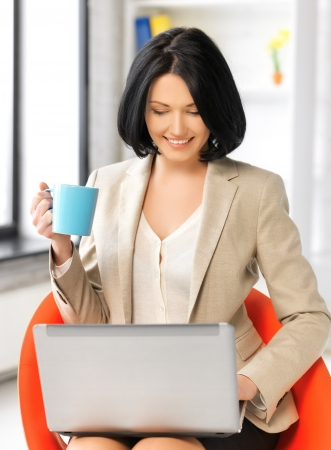 picture of businesswoman at home with laptop and cup photo