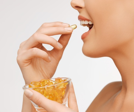 fish oil: closeup picture of woman with vitamins