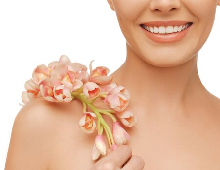 closeup picture of woman s shoulder and hands holding orchid flower photo