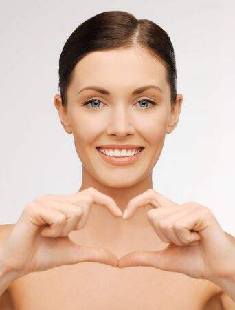 bright picture of beautiful woman showing heart shape photo