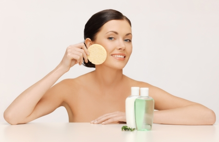 picture of woman with sponge and cosmetic bottles photo