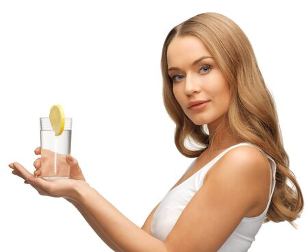 lemon water: picture of woman with lemon slice on glass of water   Stock Photo