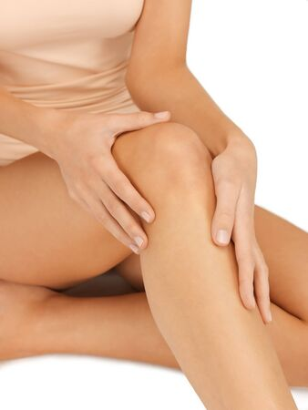 closeup picture of female hands touching knee photo