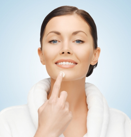 picture of woman in bathrobe applying cream Stock Photo - 17450330