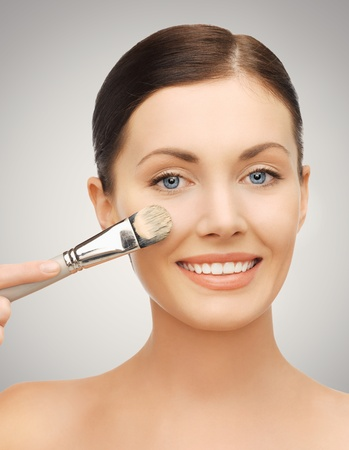 foundation: bright closeup portrait picture of beautiful woman with brush Stock Photo
