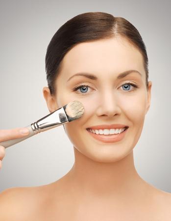 mujer maquillandose: closeup brillante retrato de la mujer hermosa con el cepillo Foto de archivo