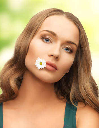 picture of beautiful woman with camomile in mouth photo