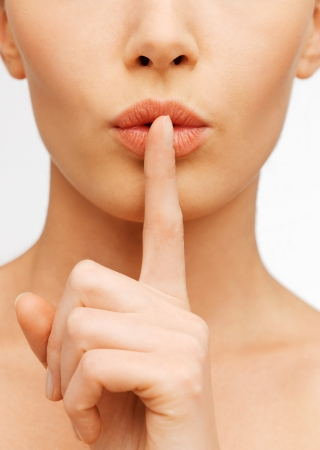 quiet adult: closeup picture of woman making a hush gesture