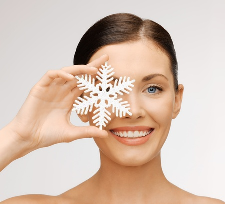 cold weather: bright picture of beautiful woman with snowflake