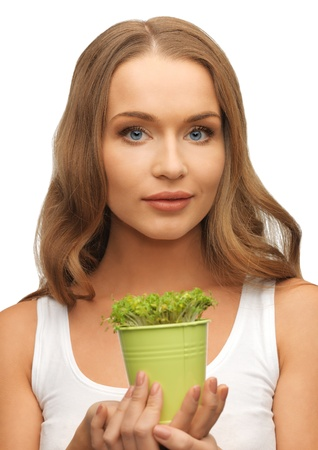 bright picture of woman with green grass in pot photo