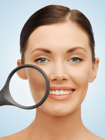 beauty spot: bright picture of beautiful woman with magnifying glass over acne