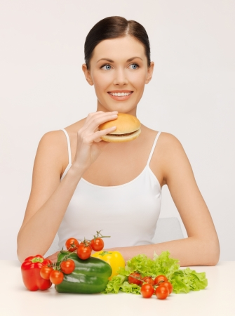 picture of beautiful woman with hamburger and vegetables photo