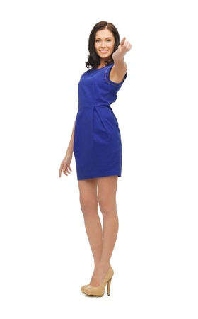lovely woman in blue dress pointing her finger photo