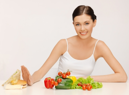 healthy choices: picture of beautiful woman with hamburger and vegetables
