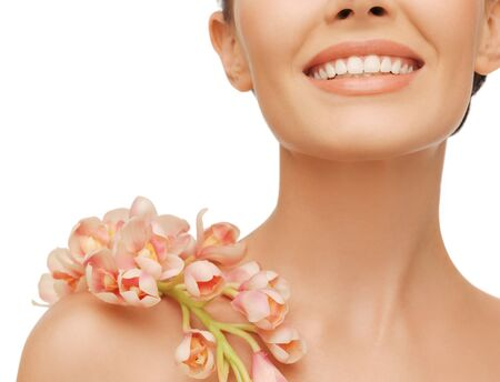 closeup picture of smiling woman with orchid flower on her shoulder photo