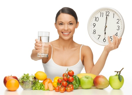 nourish: beautiful woman with healthy food water and clock Stock Photo