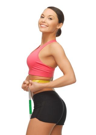 cintura perfecta: imagen de la mujer deportiva que mide su cintura