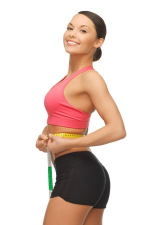 picture of sporty woman measuring her waist photo