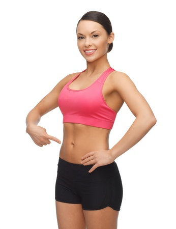 pointing finger: beautiful sporty woman pointing finger on her belly Stock Photo