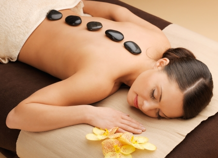 picture of woman in spa salon with hot stones photo