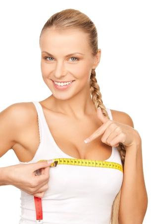 Foto de mujer joven hermosa que mide su pecho Foto de archivo