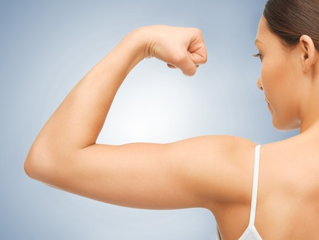 closeup picture of sporty woman flexing her biceps photo