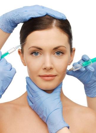 cosmetologies: picture of woman face and beautician hands with syringes