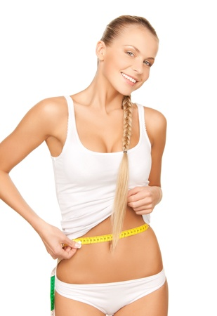 body care: picture of young beautiful woman measuring her waist
