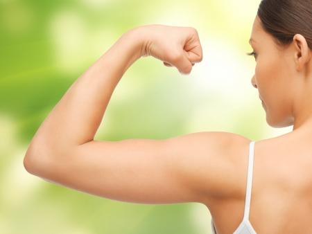 buena salud: cuadro del primer de la mujer deportiva flexionando sus bíceps Foto de archivo