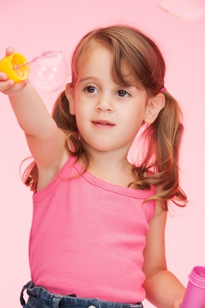 bright picture of beautiful litle girl with soap bubbles photo