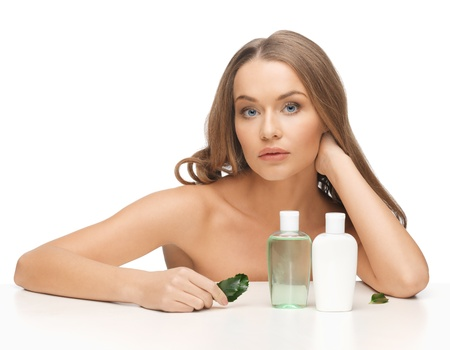 picture of woman with cosmetic bottles and leaf photo