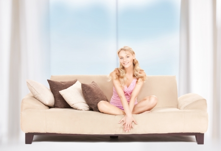 one of a kind: bright picture of happy woman on sofa Stock Photo