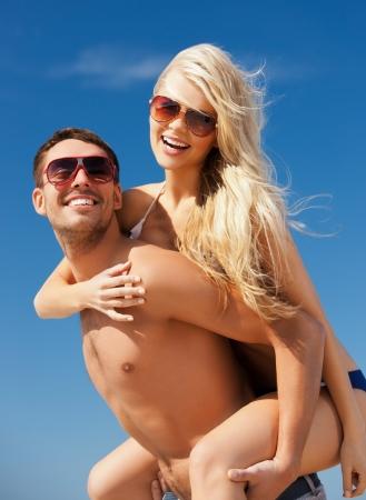 is playful: imagen de una pareja feliz en gafas de sol en la playa