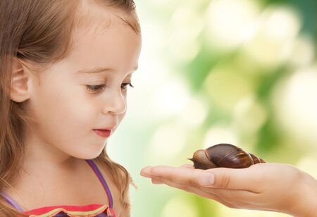 bright picture of beautiful litle girl with snail photo