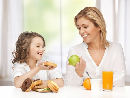 mother and daughter with healthy and unhealthy food Stock Photo - 18004924