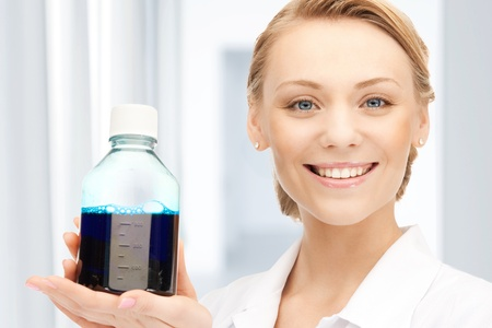 female lab worker holding up bottle with blue liquid photo