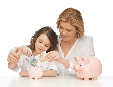 mother and daughter with piggy banks and paper money photo