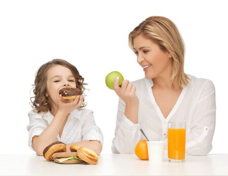 mother and daughter with healthy and unhealthy food photo