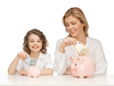 finance girl: mother and daughter with piggy banks and paper money