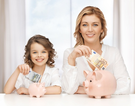 dinero euros: madre e hija con alcanc�as y billetes Foto de archivo